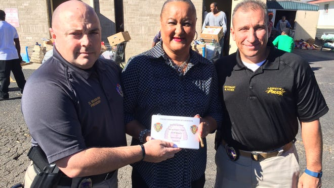 Dorian Brabham hands Kitty Joseph 50 vouchers for turkey dinners from the Police Association of Lafayette