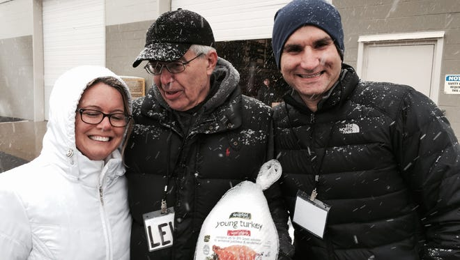 From left, volunteer Barb Edwards joins coordinator Lew Elbert and donor Greg Yatooma at a 1,000-turkey giveway in Pontiac