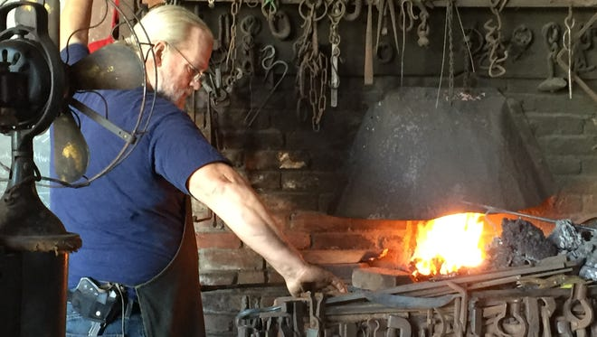 John Austin Ellsworth, 63, reaches for a tool at his coal-fired forge in Lewes on Saturday, Nov. 21, 2015. Ellsworth has been a blacksmith for decades.