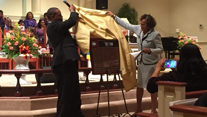 The Rev. Walter L. Brown, Jr. and Tommie Kirkendoll reveal a plaque celebrating St. Paul Christian Methodist Episcopal Church's 130th anniversary.