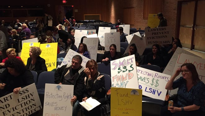 Supporters of Legal Services of the Hudson Valley display signs at the Nov. 24 hearing on the proposed Westchester County budget.