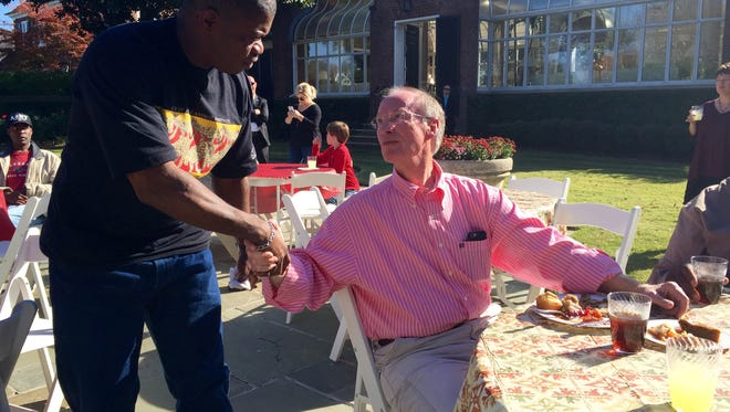 Avery Berry, a resident of Friendship Mission shelter in Montgomery, shakes hands with Alabama Gov. Robert Bentley, right, Friday, Nov. 27, 2015, at Wynfield Estate in Montgomery, Ala. Bentley invited a group from a Montgomery homeless shelter for a post-Thanksgiving meal Friday on the grounds of a state-owned estate. (AP Photo/Kim Chandler)