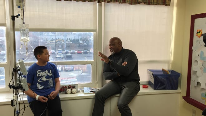 Cecil Fielder, right, a member of the New York Yankees 1996 World Series team, visits with 11-year old Michael Rankin of Toms River, a leukemia patient at Unterberg Children's Hospital at Monmouth Medical Center on Dec. 7, 2015. Fielder was handing out Hess Toy Truck's to children.
