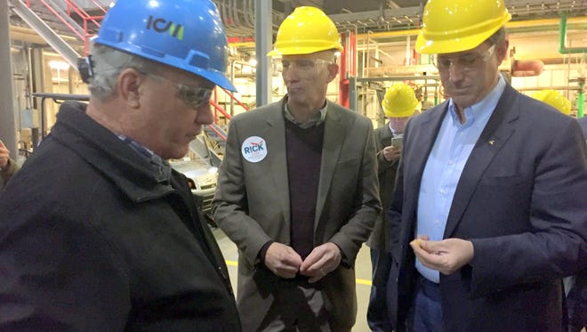 Former U.S. Sen. Rick Santorum, right, examines dried distillers' grain, which is obtained during the production of corn-based ethanol, during a tour of the Lincolnway Energy plant in Nevada, Ia., on Tuesday. Dried distillers' grain is fed to livestock. On the left is plant manager David Sommerlot, and in the center is state Rep. Walt Rogers, R-Cedar Falls, who is state director of Santorum's presidential campaign