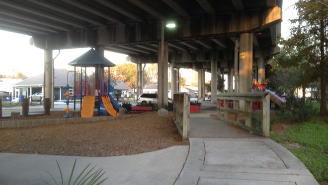 Paved paths and playground equipment make up a park under the U.S. 90 bridge in Berwick, LA.