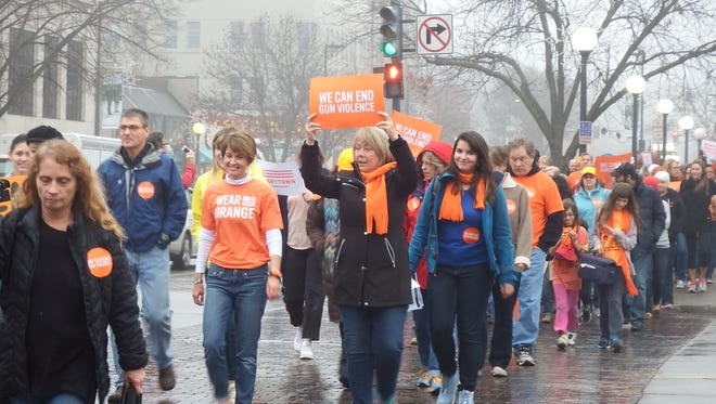Members and supporters of Moms Demand Action for Gun Sense in America march through downtown Iowa City Saturday morning as apart of their End Gun Violence rally and march on Dec. 12, 2015.