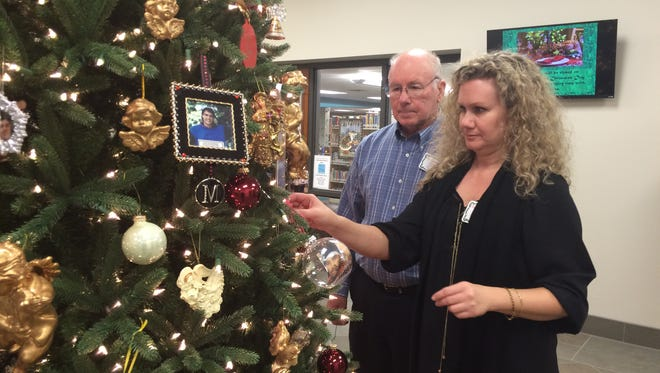 Victoria Clary hangs an ornament in honor of her brother Sandy Aydlett while her father looks on during last week's ceremony.