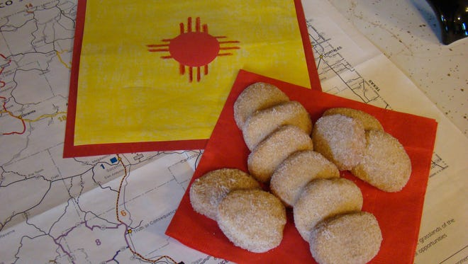 """Seen here is a sample of  'Polly's Biscochitos,"""" posing on top of a New Mexico map and by the symbol of the state, the Zia."""