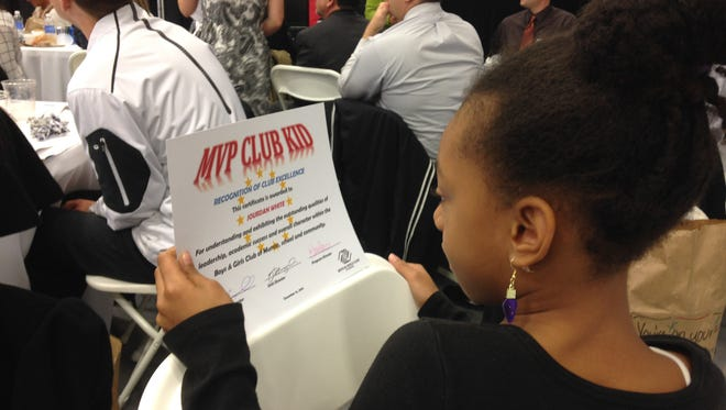 Jourdan White, a third grader at East Washington Academy, looks at her MVP Club Kid award. About 275 community members attend the Boys & Girls Club of Muncie Great Futures Recognition Luncheon.