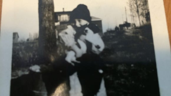 This grainy photo is of Wayne Clark as a boy. It looks as if he is holding a puppy.
