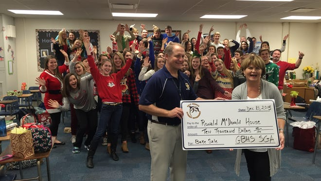 Gulf Breeze High School students, who are members of the Student Government Association, pose after presenting Ronald McDonald House Executive Director Judy Burns with a check for $10,000 on Wednesday in their classroom.