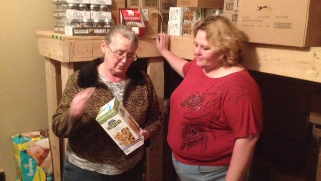Pastor Barbara Buttram and her mother, Dorothy Bradley, examine a box of healthy snack bars in the pantry of the food bank they operate out of the Carrizozo Assembly of God church.