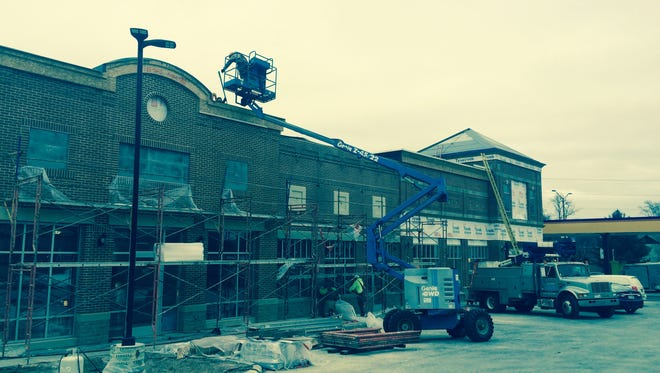 Crews work to finish The Store at the corner of Third Avenue and Clark Street in Wausau on Dec. 17, 2015.