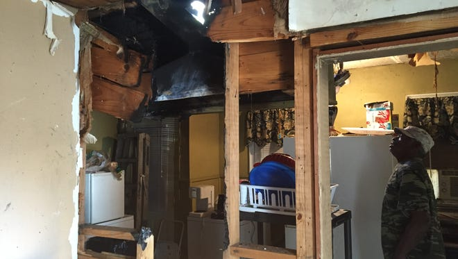 John Taylor gazes up through a hole burned through his ceiling and into his attic in November.