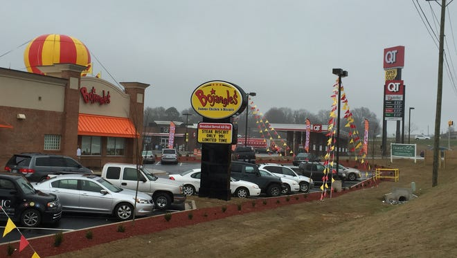 Cars filled the new Bojangles' parking lot at Harrison Bridge Road Monday morning on the store's opening day of business. The new QT, background, opens Thursday.