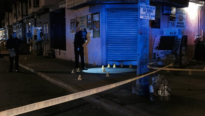 Wilmington police take photos of shell casings outside of Concord Deli in Wilmington Monday night.