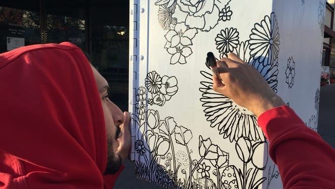 Albert Fraide, 24, at work on his visual garden for the Salinas Urban Art Project.