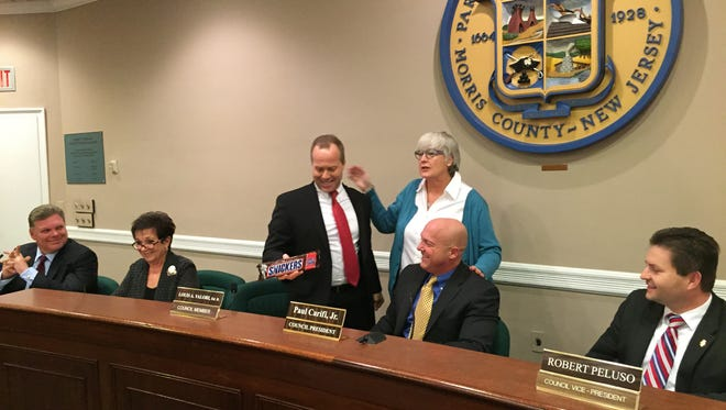 Newly-elected Parsippany Council President Louis Valori accepts an oversize Snickers bar from Busines Administrator Ellen Sandman Tuesday during the township reorganization meeting. Seated and looking on, from left, are Township Attorney John Inglesino and council members Loretta Gragnani, Paul Carifi Jr. and Robert Peluso.