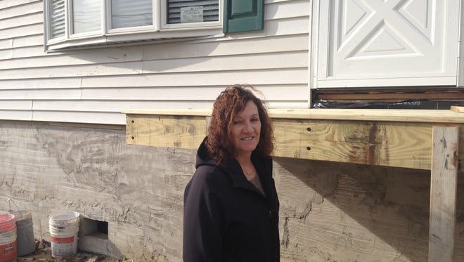 Kristine Eckert stands in front of her Brick home, which is being raised.