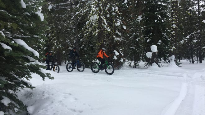 A group of fat bike riders pedals on the snow near Brockway Summit at Lake Tahoe.
