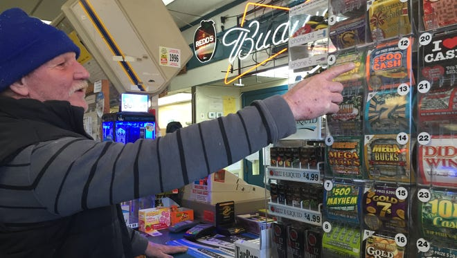 Weaverville resident Jeff Dickman buys a Powerball ticket on Wednesday at BJ's Food Mart in West Asheville.