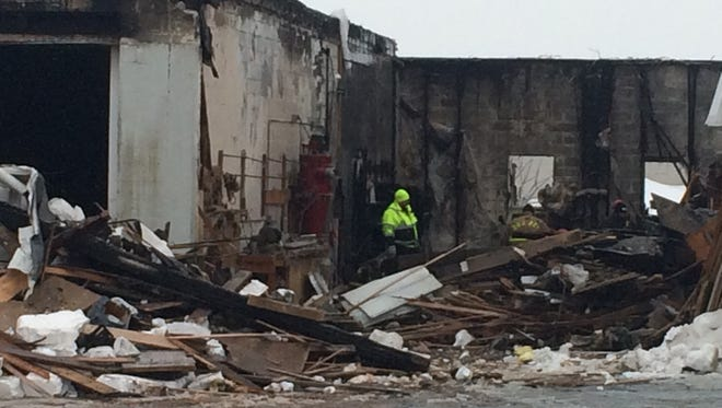 Fire investigators examine the damage after a Tuesday night fire at Windows of Wisconsin on Velp Avenue in Green Bay.