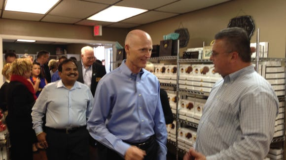 Gov. Rick Scott, center, speaks with Jim Frazier, (far