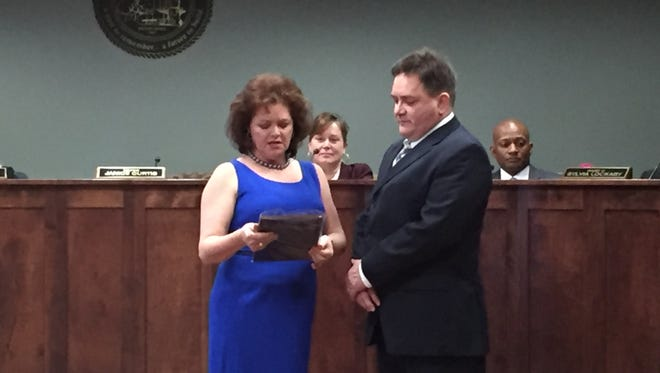New Simpsonville Mayor Janice Curtis, left, presents a plaque to her husband George Curtis for his eight years of service on City Council.