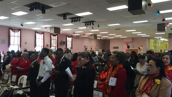 Attendees sing along at the Central Jersey Club's Martin Luther King Jr. Day celebration Monday afternoon at the Mount Carmel Catholic School in Asbury Park.