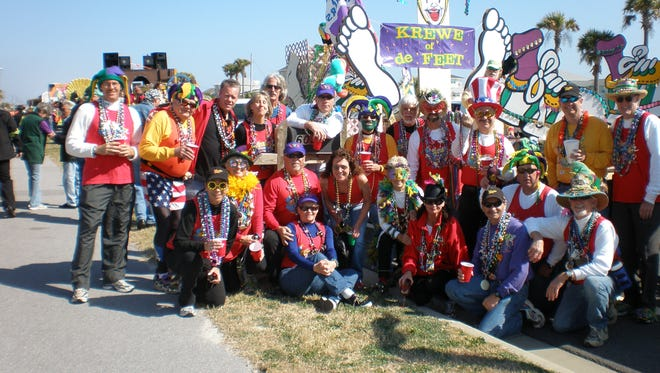 The Krewe of de Feet poses next to its float.