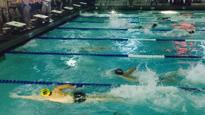 Swimmers race down the lanes at the District 1-5A swim meet Thursday night at the Socorro Student Activities Complex Aquatic Center.