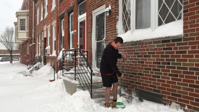 Jason Brehouse braves the cold in shorts to sweep up his front stoop in the 800 block of Judson Street in Philadelphia on Saturday morning. Heavy snow paralyzed wide sections of the East Coast, with extensive delays reported on roadways and transit systems.
