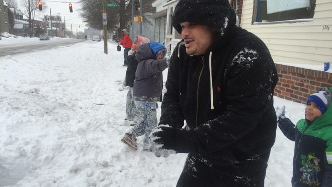Julio Rosa plays with his children as they have a snowball fight on Saturday in Wilmington. Jo Jo Rosa is 7, Jose Rosa is 8, and G Rosa is 4.