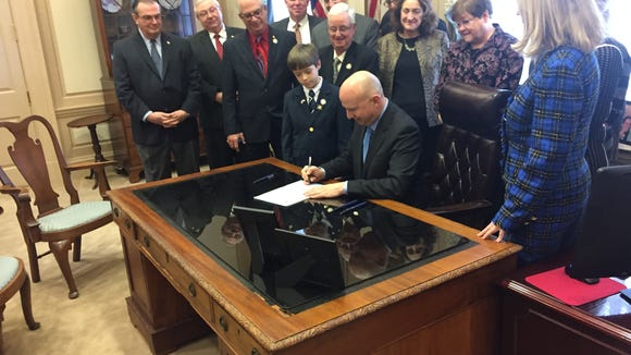 Gov. Jack Markell, flanked by legislative leaders, signs a bill overhauling the state's corporate income tax Wednesday.