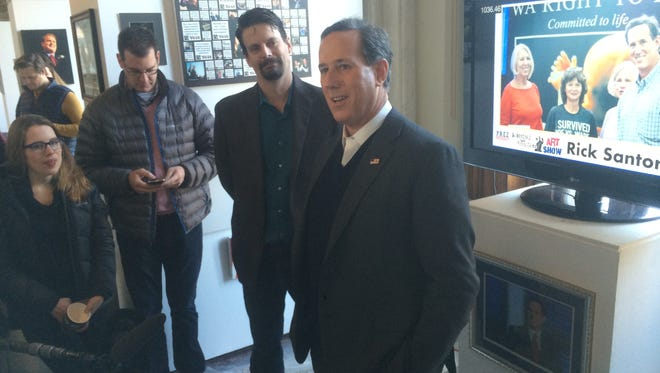 Rick Santorum, right, tours an Iowa caucus photo exhibit Friday at the Polk County Administration Building.