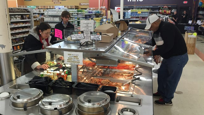 Customers pick food from a buffet table at the newly renovated Better Health Store in the Frandor Shopping Center