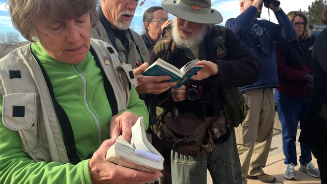 Birders Margaret Fahey, John Mueller and John Free, from left, look through field guides as they participate in a St. George Winter Bird Festival field trip Friday, Jan. 29, 2016 in St. George.