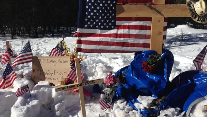 A makeshift roadside memorial for rancher LaVoy Finicum stands on a highway north of Burns, Oregon Sunday, Jan. 31, 2016. Finicum was killed Tuesday night in a confrontation with the FBI and Oregon State Police on a remote road. Four people occupying the Malheur National Wildlife Refuge held their position Sunday. They have demanded that they be allowed to leave without being arrested.