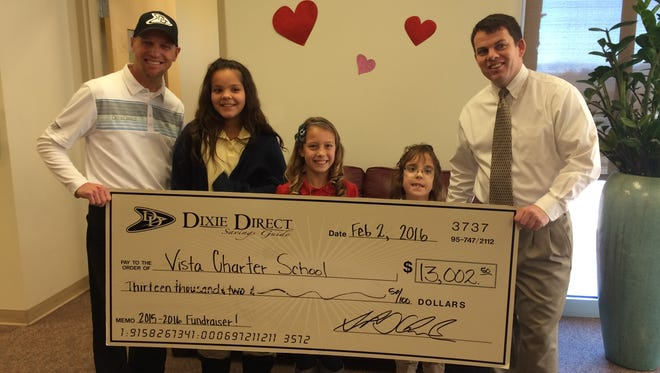 Dixie Direct owner Tony Chambers, Madisen Hone, Zoie Perkins, Olivia Mackay and Vista School Principal Sam Gibbs pose with a check from the Dixie Direct school fundraising project.