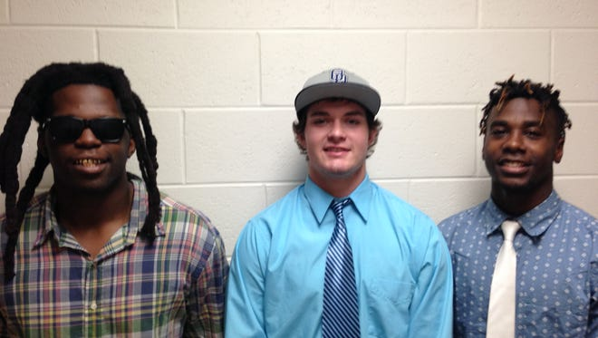 From left, Donovan Gayle, Zack Lackman and Toquan Bridley celebrate making their college destinations official at Dunbar High School.