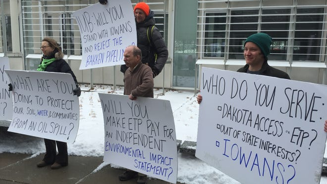 Anti-pipeline protesters stand outside the Iowa Utilities Board's offices Monday in Des Moines before the board began deliberations on the proposed Bakken crude oil pipeline, which would pass through 18 Iowa counties.