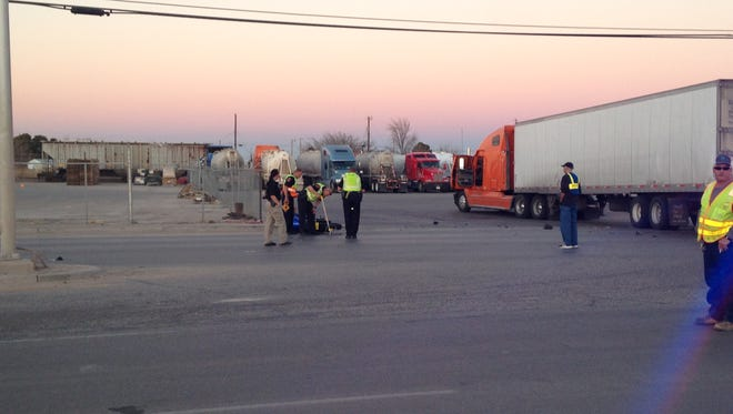 Police investigate the scene where a motorcycle and 18-wheeler crashed Wednesday afternoon on the Loving Highway.