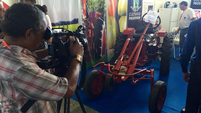 Cuban reporters hover around a tractor made by Cleber, an Alabama-based company, during the International Trade Fair outside Havana on Nov. 2, 2015. Cleber won approval from the Obama administration to begin construction of the tractors in Cuba.