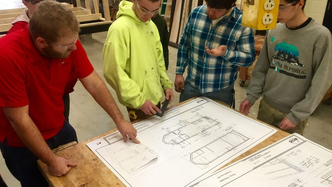 Robert Boenisch, left, technology education teacher at Oostburg High, examines blueprints for a tiny house project with multiple construction students.