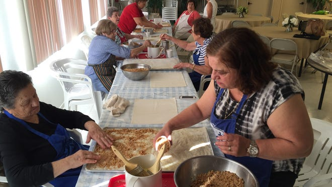 Stacy Argyros, right, and her mother, Eleni, work together to make a tray of baklava.