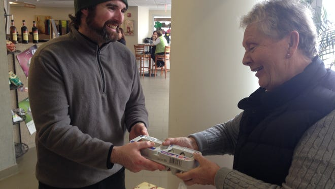 James Kelley of Modern Dinosaur Farm sells a batch of eggs to Barb Hookway Wednesday at the Marshall Area Farmers Market at Oaklawn Hospital.