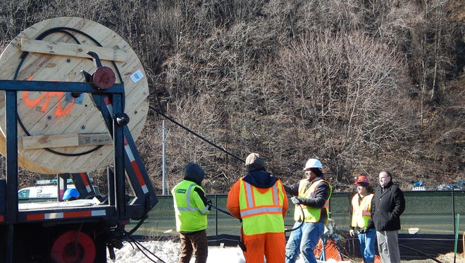 Employees of Hylan Datacom & Electrical pull York-based United Fiber and Data's fiber-optic line into the tunnel to run it into New Jersey.