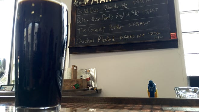 A pint of The Great Porter rests on the bar in front of Man Skirt Brewing's draft list.