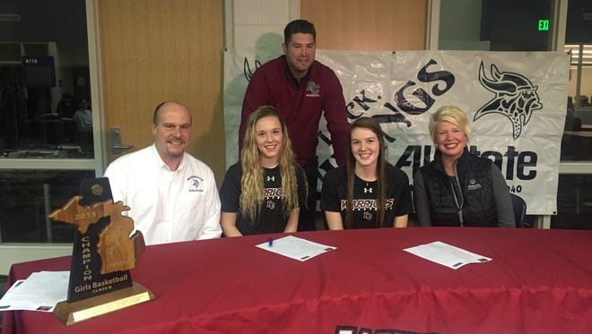 Marysville Athletic Director Tom Valko alongside daughters Madison (left) and Devan and his wife Dawn Valko smile at a signing event at Marysville High School. The Valko sisters signed to play for coach Brent Wichtner (back row) at Rochester College.
