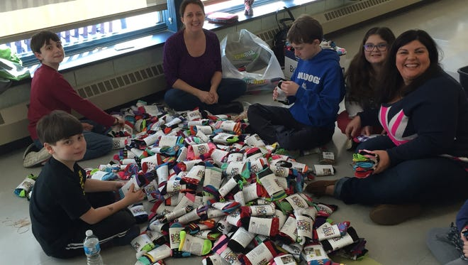 Students work mismatching socks in preparation for World Down Syndrome Awareness Day. More than 500 people mismatched 50,000 socks for the event in March.